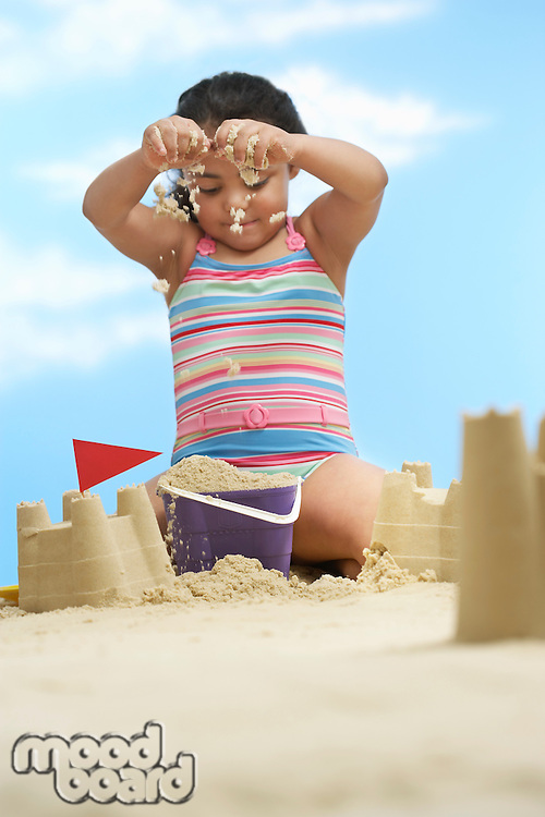 Girl (7-9 years) building sand castles on beach