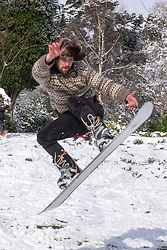 @Licensed to London News Pictures 27/02/2018.Tunbridge Wells, UK. As hundreds of schools are closed and travel disruptions in the county local residents of Royal Tunbridge Wells enjoying sledging and snowboarding in the bright sunshine and heavy snow showers crossing the South East of the UK today at Dunorlan Park.  Photo credit: Manu Palomeque/LNP