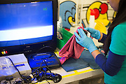 An employee cleans a Sega Genesis game at the GameStop retro classics console games refurbishment center in Grapevine, Texas on June 24, 2015. (Cooper Neill for Mashable)