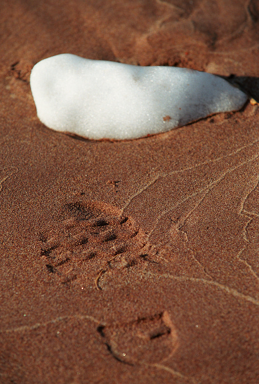 A PIECE OF LAKE SUPERIOR PACK ICE MELTS ON A SAND BEACH NEAR A BOOT PRINT IN SPRING NEAR MARQUETTE MICHIGAN.