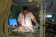 Dr. Jose Arias-Camison examines an infact in the NICU.