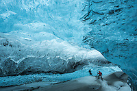 Photographers exploring and photographing an Ice Cave in Vatnajökull glacier, Southeast Iceland.