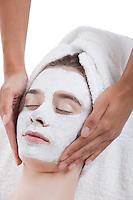 Young woman receiving facial treatment at spa