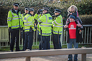 A man and his child try to persuade passing motorists as police stand by - Protestors block roads on the routes into Heathrow from the M4. Several are arrested.
