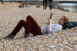 © Licensed to London News Pictures. 27/03/2015. Brighton, UK. Members of the public enjoy their lunch break sunbathing on Brighton Beach today, Friday 27th March 2015. Photo credit : Hugo Michiels/LNP