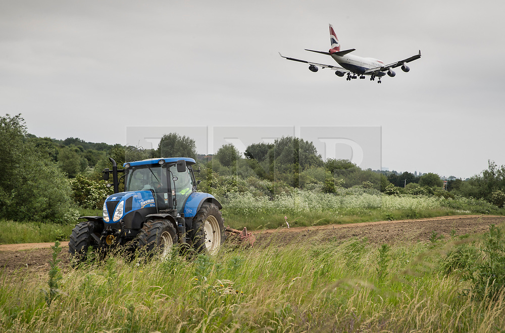 © Licensed to London News Pictures. 05/06/2018. London, UK. A Boeing 747 jumbo jet comes into land at Heathrow airport near a tractor ploughing a field. The government has announced a third runway will go ahead at Heathrow. Photo credit: Peter Macdiarmid/LNP