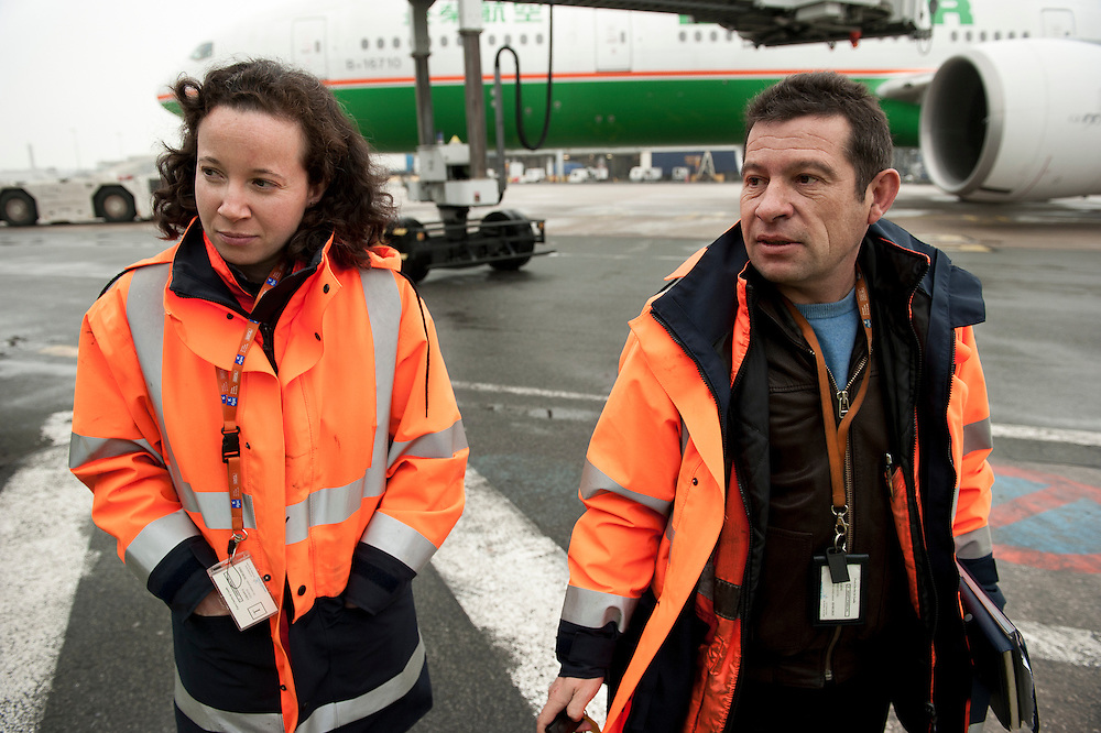 Inspectors Emmanuel and  Nesrine on the airport Roissy Charles de Gaule near Paris. With one order, they can immobilise a Boeing or delay the taking off for 300 passengers on an intercontinental flight. When Operating Technical Inspectors (CTE) get aboard , it is always in pairs and always unexpected. That day, Emmanuel Lain&eacute; (R) and Nesrine Chkioua (L), one of the only three women in France to do this job, control an international flight to Taipei and a cargo plane bound for Lebanon.<br /> <br /> D&rsquo;un ordre, ils peuvent immobiliser un Boeing ou retarder le d&eacute;collage des 300 passagers d&rsquo;un long courrier. Quand les contr&ocirc;leurs techniques d&rsquo;exploitation (CTE) d&eacute;barquent, c&rsquo;est toujours en bin&ocirc;me et toujours &agrave; l&rsquo;improviste. Ce jour-l&agrave;, Emmanuel Lain&eacute; (D) et Nesrine Chkioua (G), l&rsquo;une des 3 femmes CTE en France, passent au crible un vol international pour Taipei et un avion de fret en partance pour le Liban.