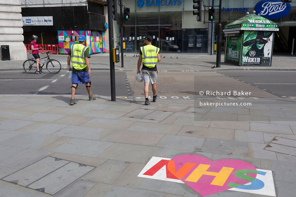 During the UK's Coronavirus pandemic lockdown and on the day when a further 255 deaths occurred, bringing the official covid deaths to 37,048, <br /> two workmen walk through Piccadilly Circus where an NHS-supporting stencil (National Health Service) has been stuck to the ground, on 26th May 2020, in London, England.