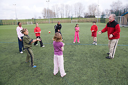Trainer; with a circle of children; throwing and catching a tennis ball to one another on a playing field at their local leisure centre,