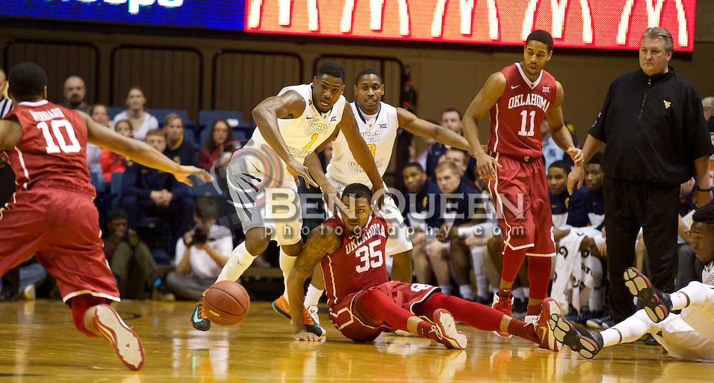 West Virginia Mountaineers forward Jonathan Holton (1) and Oklahoma Sooner forward TaShawn Thomas (35) dive for a loose ball during the first half at the WVU Coliseum.