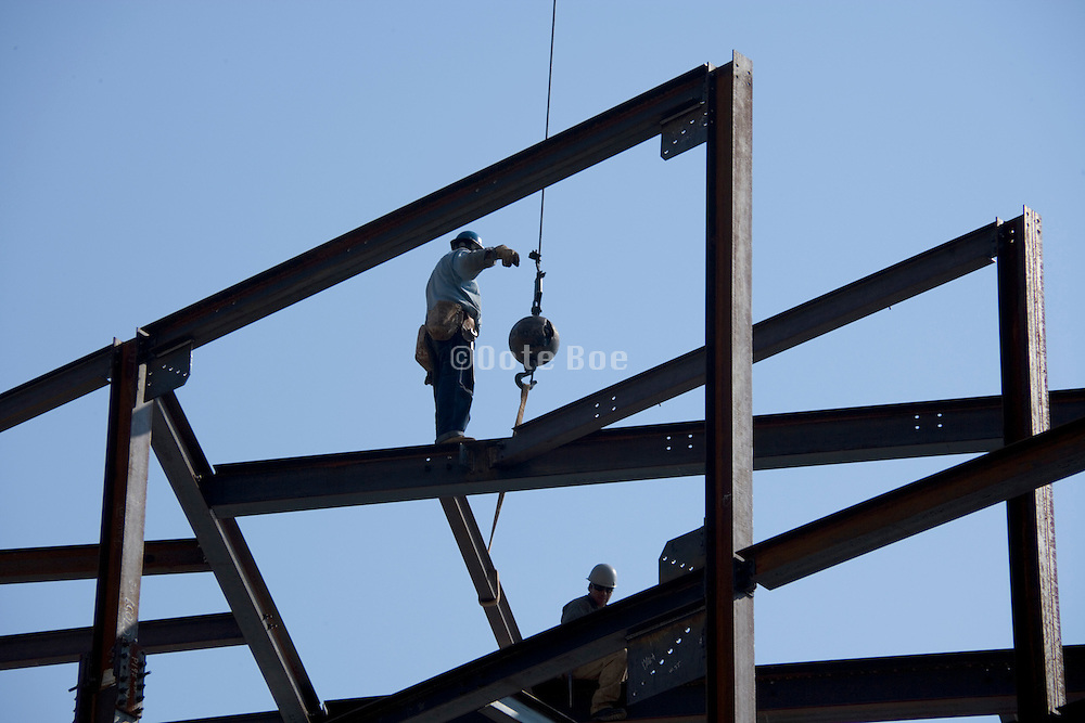 ironworker standing on top of a steel framework while guiding a girder into place
