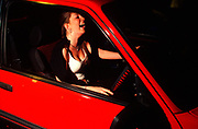 A girl sat in her car, laughing, Girlracers, Southend, UK 2004