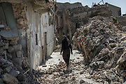 Kasim, 75, walks towards his house that was destroyed by an airstrike in the heavy fighting to liberate the Old City of Mosul last July. <br /> <br /> He says he's never seen a battle like the battle for Mosul: &ldquo;Bombs were falling like rain, thousands were killed by airstrikes,&quot; he says.