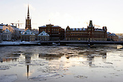 Sheets of ice flow through the centre of Stockholm, Sweden, showing the old town in the background.