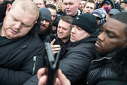 "© Licensed to London News Pictures . 18/03/2018 . London , UK . TOMMY ROBINSON (centre) is pushed through the crowd as he leaves . 1000s including supports of alt-right groups such as Generation Identity and the Football Lads Alliance , at Speakers' Corner in Hyde Park where Tommy Robinson reads a speech by Generation Identity campaigner Martin Sellner . Along with Brittany Pettibone , Sellner was due to deliver the speech last week but the pair were arrested and detained by police when they arrived in the UK , forcing them to cancel an appearance at a UKIP "" Young Independence "" youth event , which in turn was reportedly cancelled amid security concerns . Photo credit: Joel Goodman/LNP"