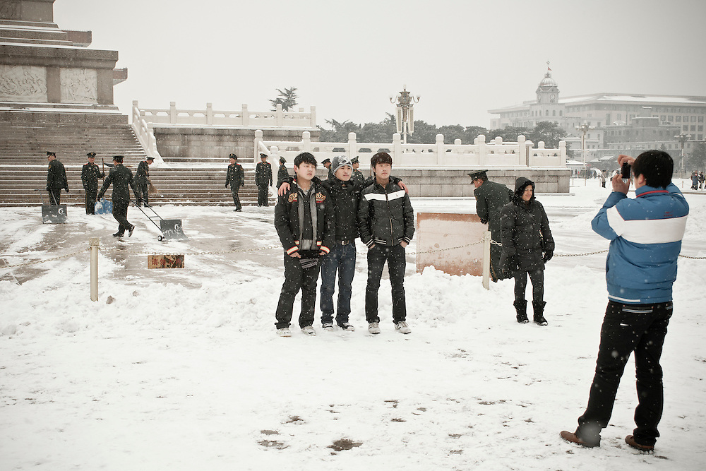 A group of chinese youngmen are posing in front of the People's revolution heroes monument (being clening by guards ) on Tiananmen square  after a snowfall that local authorities say they have artifically provoked to fight the exceptional drought in northern China. February 10 2011.