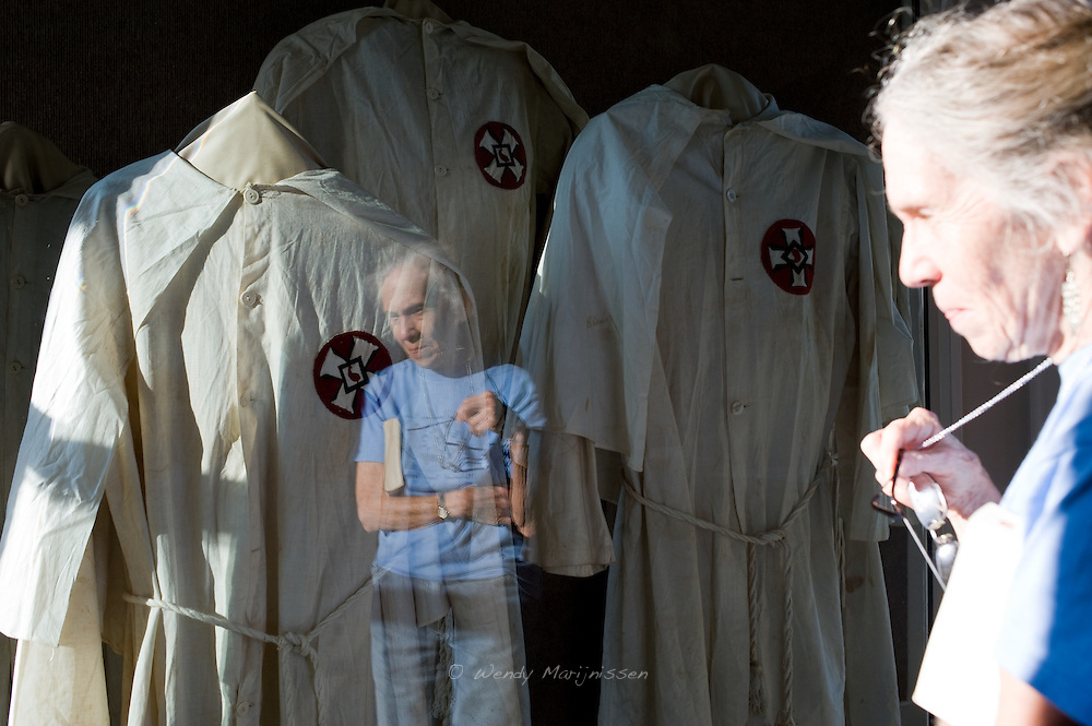76 year old Carla Heath works at the Legacy museum in Lynchburg, showing the local African-American history of the neighborhood. The Ku-Klux-Klan suits are part of the museum display telling the story of racism in the area. Virginia, USA, 2011