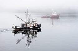 Fishing boats slowly make their way through the fog in Auke Bay near Juneau, Alaska.