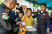 "Thai immigration police check the temporary ID cards of undocumented Cambodian workers at the temporary ""one stop service center"" in the Bangkok Youth Center in central Bangkok. Thai immigration officials have opened several temporary ""one stop service centers"" in Bangkok to register undocumented immigrants and issue them temporary ID cards and work permits. The temporary centers will be open until August 14."