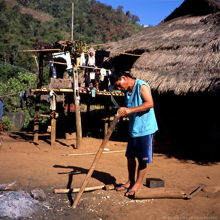 Man cutting wood at the Akha village Huei Naam Kun that is located in the mountains near Chiang Rai.