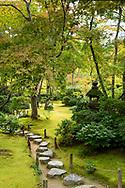Stepping stones on a path through  a moss garden and a wooded area of the Okochi Sanso Villa Garden,  Arashiyama, Kyoto, Japan