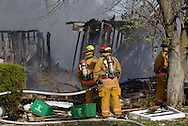 Firefighters look over the scene near a house in the 300 block of Wayne Drive that was destroyed by what appears to be a gas-line explosion in Fairborn, Saturday, November 12, 2011.