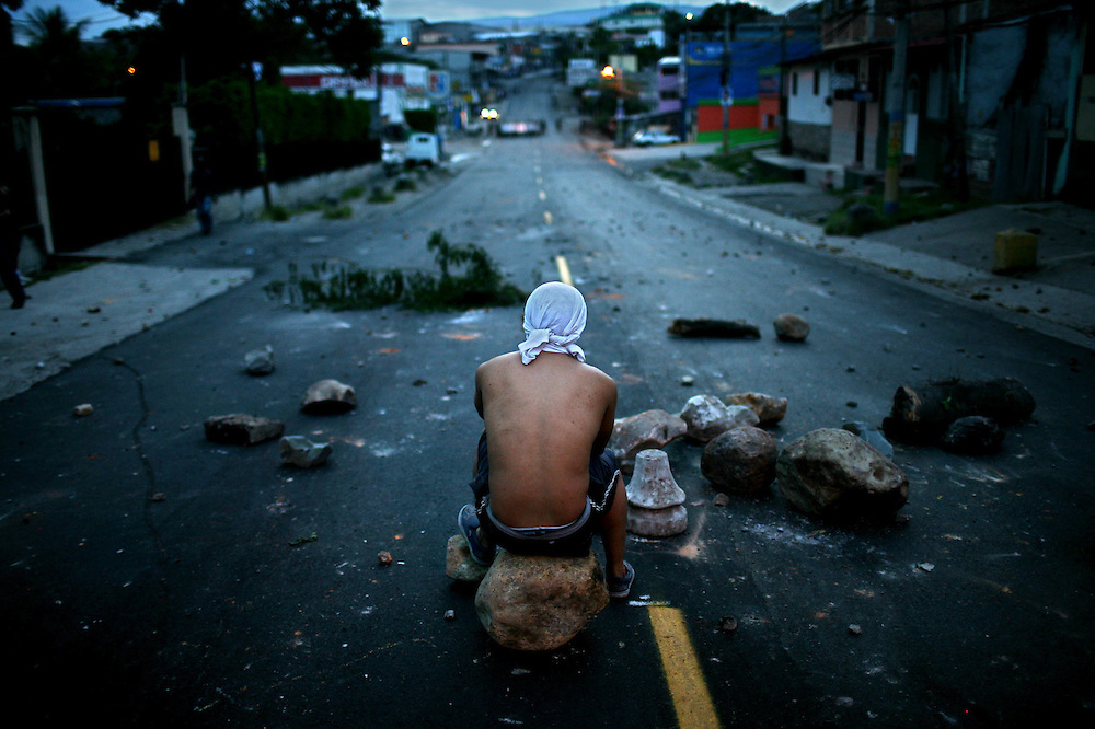 A supporter of Honduras's ousted President Manuel Zelaya sits on a barricade during a protest inTegucigalpa, Tuesday, Sept 22, 2009. Honduras' airports and borders were closed Tuesday, while baton-wielding police fired tear gas to chase thousands of demonstrators away from the embassy where Zelaya is holed up to avoid arrest.