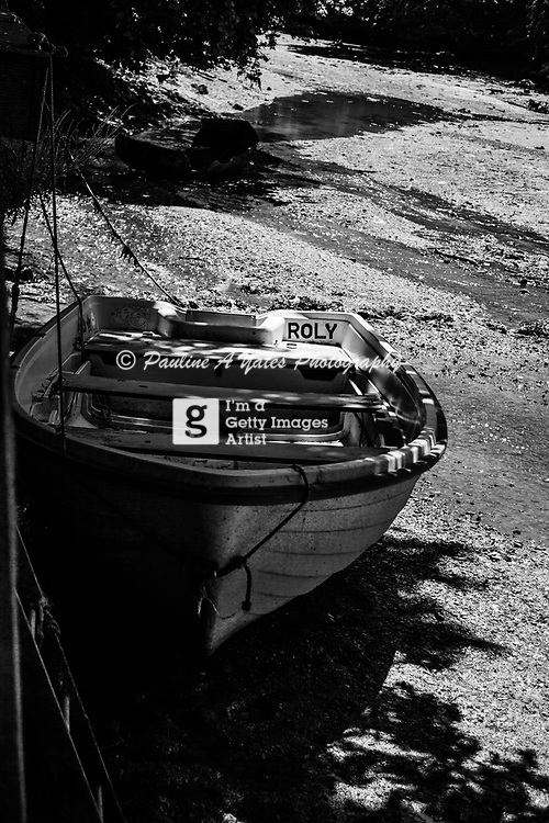 A boat named Roly stranded on the estuary mud flats, hidden in the shadows