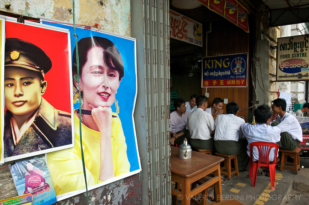 Burmese men on a conversation at a teashop in the capital, next to Aung San and Aung San Suu Kyi posters up for sale..Yangon, Myanmar. 2012