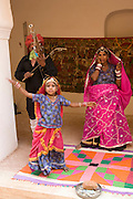 India, Rajasthan, Jaipur, Amber fort built 1592 Child performer in traditional vivid clothes entertaining the tourists