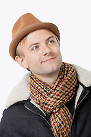 Happy young Caucasian man in warm clothing looking away against white background