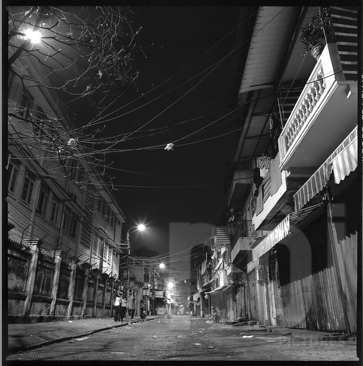 A small group of people stand on the side of an empty street by night. Hanoi, Vietnam, Asia
