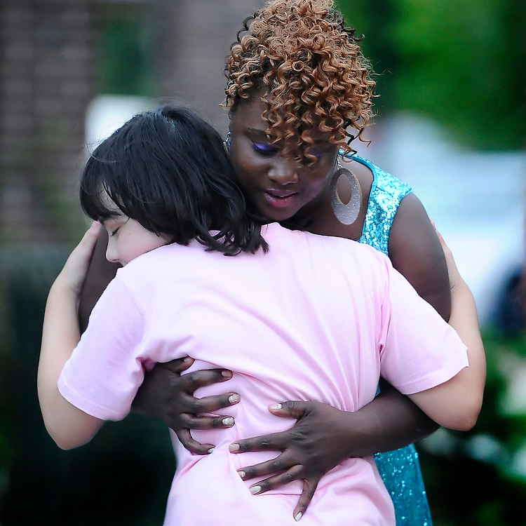 Nekita Waller receives a hug from her biggest fan, a young girl named Fiona, during a singing competition.  Nekita won the competition.