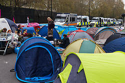 Dozens of police wait in vans on the outside of the occupied zone as hundreds of environmental protesters from Extinction Rebellion occupy Marble Arch, camping in the square and even on the streets, blocking access to traffic on Park Lane and Oxford Street in London's usually traffic-heavy west end. . London, April 16 2019.