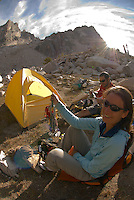 A young couple sorts climbing gear while at camp in the Sawtooth Mountains, Idaho.