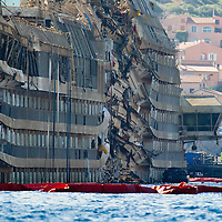 ISOLA DEL GIGLIO, ITALY - SEPTEMBER 18:  The previously submerged severely damaged right side of the Costa Concordia is seen  on September 18, 2013 in Isola del Giglio, Italy. The vessel, which sank on January 12, 2012, was successfully righted during a painstaking operation yesterday morning. The ship will eventually be towed away and scrapped. ItÊwas the first time the procedure, known as parbuckling, hadÊbeen carried out on a vessel as large as Costa Concordia.  (Photo by Marco Secchi/Getty Images)