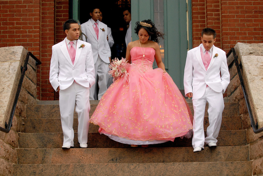 At her 15th birthday celebration, Jacqueline Serna is la quinceañera or sweet fifteen as she leaves a mass celebration at Most Holy Trinity Catholic Church in Wallingford, Connecticut on Oct. 28, 2006. Serna is escorted by chambelanes or groomsmen. At left is Jose Soto, 18, and at right is his brother, Jonathan Soto, 17. Serna's father was one of the pioneer Mexican steel workers to settle in Wallingford.
