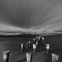 A black and white image of wooden pillars of an old pier standing motionless against a turbulent sky and sea shore turned smooth in a 2 minute long exposure. Puerto Natales, Patagonia, Chile.