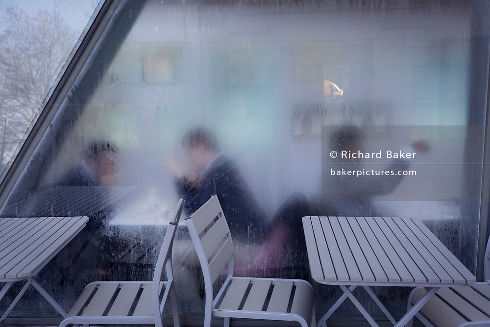 Through steamy windows, businessmen have informal talks inside a City of London bar, on 22nd January 2019, in London England.