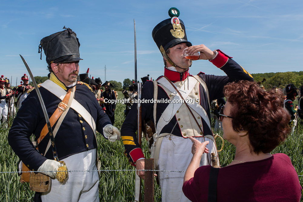 20150614 Ligny Belgium. The Battle of Ligny (16 June 1815) was the last victory of the military career of Napoleon I.Today it was re-enacted by 1500 people just a few days before the 200th birth day of Napoleon's final loss at Waterloo.Re-enactors get something to drink from a spectator  in the burning heat