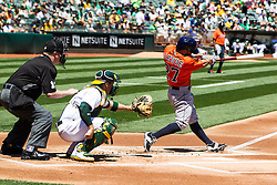 OAKLAND, CA - MAY 01:  Jose Altuve #27 of the Houston Astros hits a home run in front of Stephen Vogt #21 of the Oakland Athletics and umpire Todd Tichenor #13 during the first inning at the Oakland Coliseum on May 1, 2016 in Oakland, California. (Photo by Jason O. Watson/Getty Images) *** Local Caption *** Jose Altuve; Stephen Vogt; Todd Tichenor
