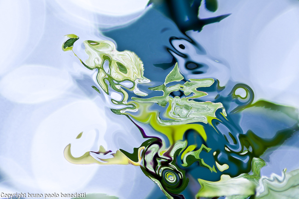 abstract reflections on the water. A like painted fluid shape in green color on water covered by spots of light reflections. Colors of the nature.