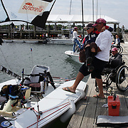 Skipper Sarah Everhart Skeels, Tiverton, RI, is helped into the boat by husband Brian Skeels before sailing with Cindy Walker, Middletown, RI, the only all female team competing in The Skud 18 class, during the C. Thomas Clagett, Jr. Memorial Clinic & Regatta at Newport, Rhode Island hosted by Sail Newport at Fort Adams. <br /> The Clagett is North America's premier event for sailors with disabilities with sailors competing in the 3 Paralympic class boats and is an integral part of preparation for athletes preparing for  Paralympic and world championship racing. Newport, Rhode Island, USA. 26th June 2015. Photo Tim Clayton