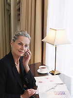 Business woman using mobile phone sitting at desk elevated view