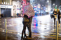 © Licensed to London News Pictures . 17/03/2017 . Cardiff , UK. A couple turn their umbrella in to the wind and embrace behind it . Revellers on a windy and wet Saint Patrick's Day night out in Cardiff city Centre . Photo credit: Joel Goodman/LNP