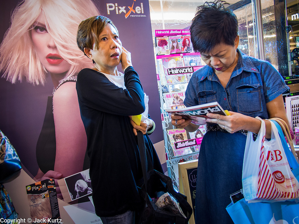 24 JULY 2013 - BANGKOK, THAILAND: A woman uses her cell phone in front of a poster for Thai manufactured hair care products at the Hairworld Festival in Siam Paragon, an upscale shopping mall in Bangkok, Thailand.        PHOTO BY JACK KURTZ