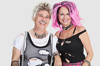 Portrait of cheerful senior punk couple with arm in arm over gray background