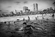 Ali Ayrhim, 18, paddles out from Gaza City, Gaza Strip. During the summer Palestinians flock to the beaches in huge numbers as these represent the only real recreational spaces in the coastal enclave.