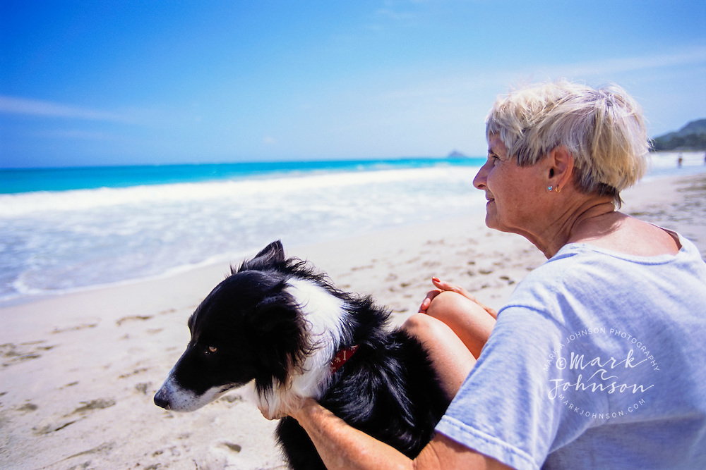 Oahu, Hawaii, USA --- Elderly Woman Sitting on Beach with Dog