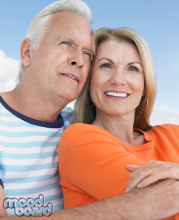 Middle-aged couple outdoors embracing and smiling